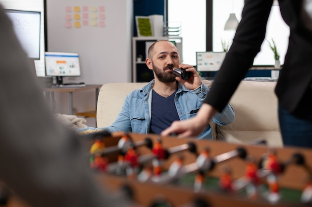 オフィスで仕事をした後、ビールを飲みながら楽しんでいる男