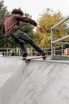 Человек веселится со скейтбордом в парке