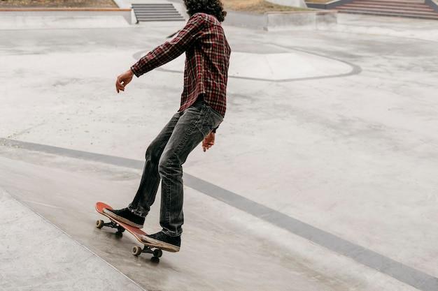 Uomo che si diverte con lo skateboard fuori nel parco
