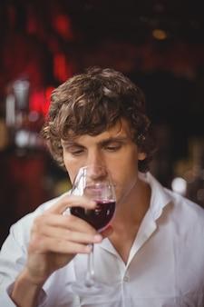 Uomo che mangia un bicchiere di vino rosso