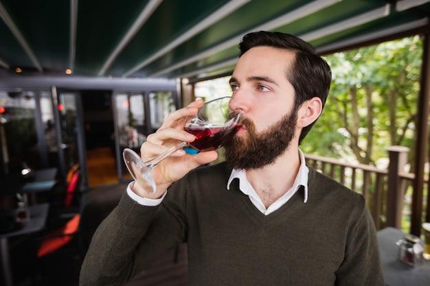 Uomo che mangia bicchiere di vino nella barra