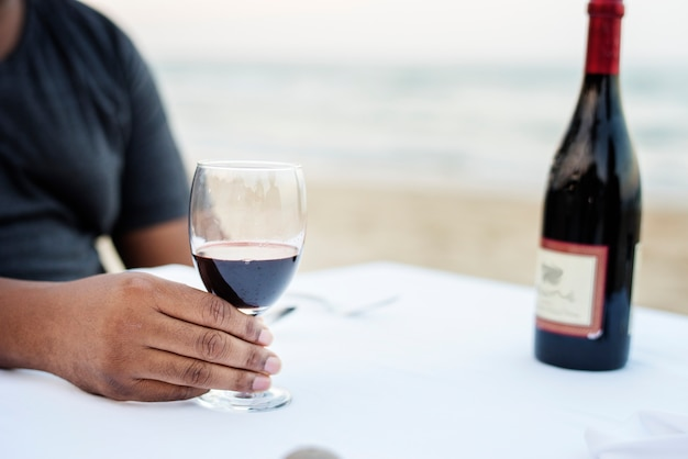 Man having a glass of wine by the sea