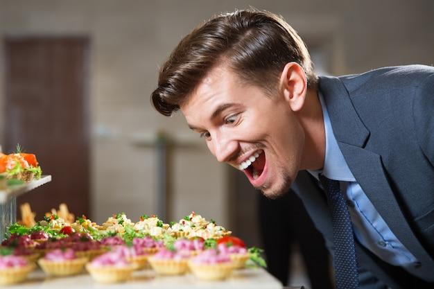 Man having great desire to eat tartlets in buffet