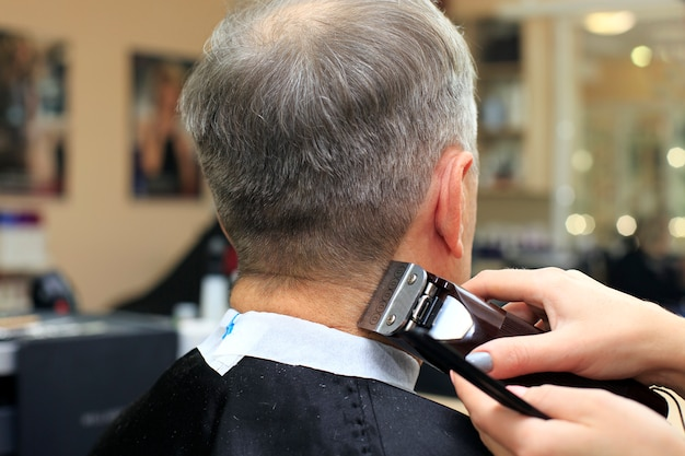 Man having a haircut from hairdresser.