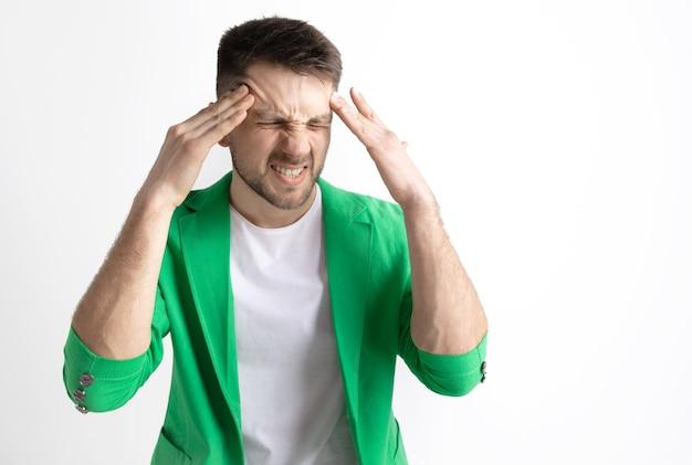 頭痛のある男。灰色の空間に孤立した痛みで立っているビジネスマン