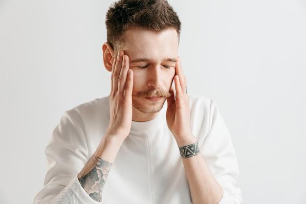 頭痛のある男。灰色のスタジオの背景に分離された痛みで立っているビジネスマン。男性の半身像。人間の感情、表情の概念