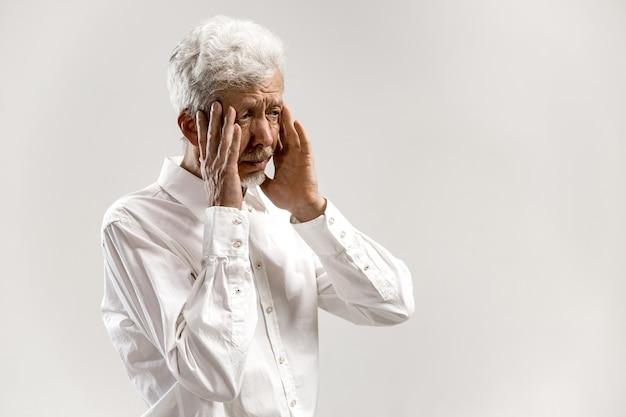 두통이있는 사람. 흰 벽에 고립 된 스트레스와 함께 서있는 비즈니스 사람. 남성 절반 길이 초상화. 인간의 감정, 표정 개념