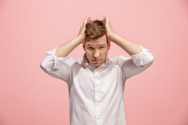 頭痛を持つ男。ピンクのスペースに分離されました。トレンディなピンクに分離された痛みで立っているビジネスの男性。男性の半身像。人間の感情、表情のコンセプト。フロント