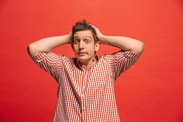 頭痛のある男。赤で隔離。トレンディな赤に孤立した痛みで立っているビジネスマン。男性の半身像