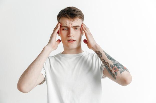 Человек болит голова. изолированный над серым валлом.