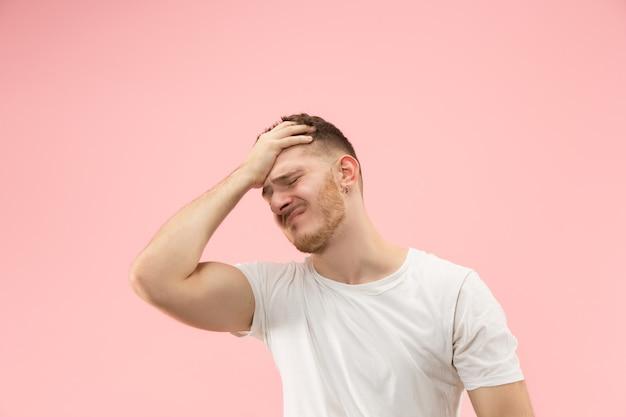 Uomo che ha mal di testa. isolato su sfondo rosa.
