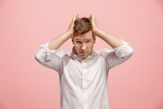 Man having headache. isolated on pink space. business man standing with pain isolated on trendy pink. male half-length portrait. human emotions, facial expression concept. front