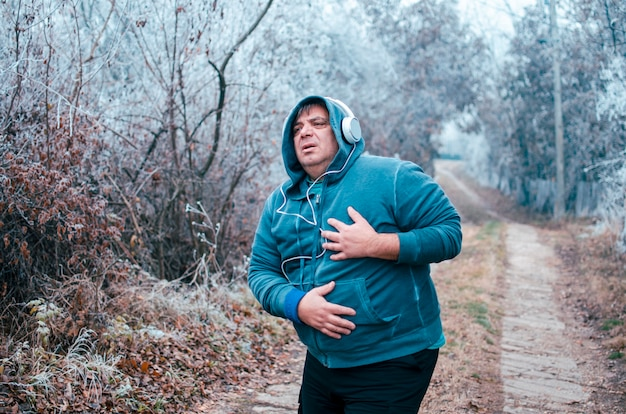 Man having heart attack or heart failure after running.mature overweight tired man on jogging outdoors