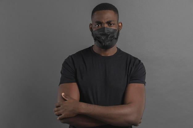 腕を組んでマスクをしている男