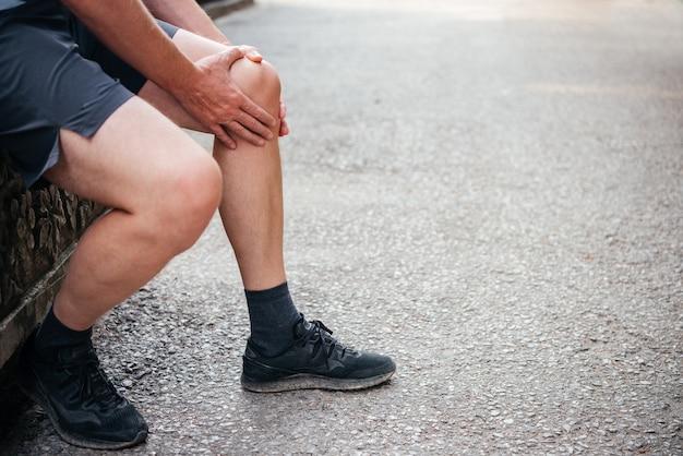 スポーツ傷害の概念を行使しながら膝の痛みを持っている男