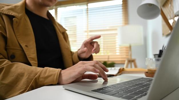 집에서 컴퓨터 노트북으로 영상 통화를 하는 남자.