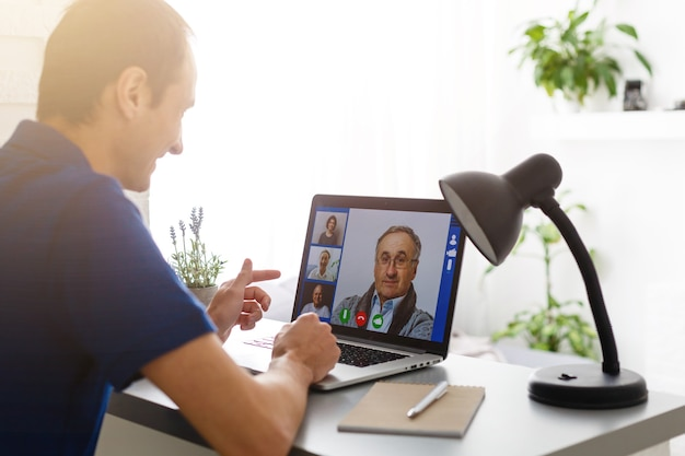 Человек, имеющий видео-чат с врачом на ноутбуке дома