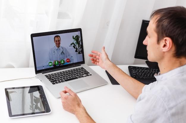 Человек, имеющий видео-чат с врачом на ноутбуке у себя дома