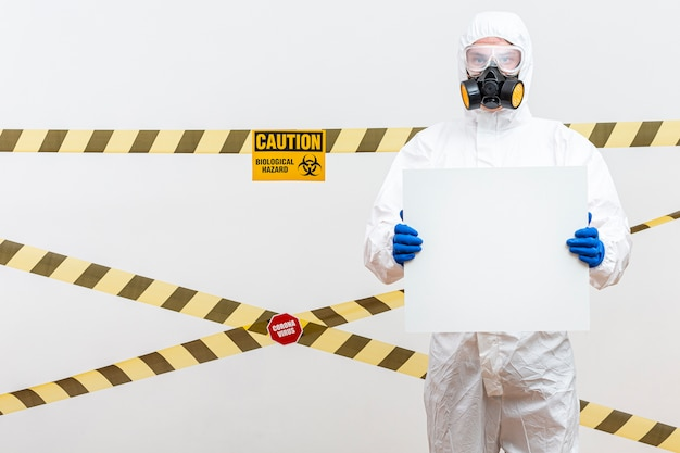 Man in hazmat suit with blank sign