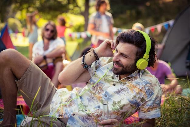 Man in headphones holding beer bottle at campsite