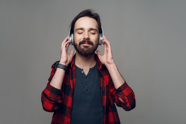 A man in headphones listens to music carefully.
