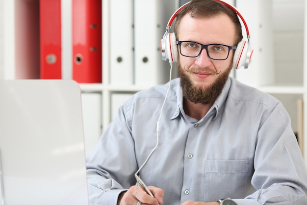 A man in headphones listens to music and learns online. makes notes in a notebook and looks at the camera