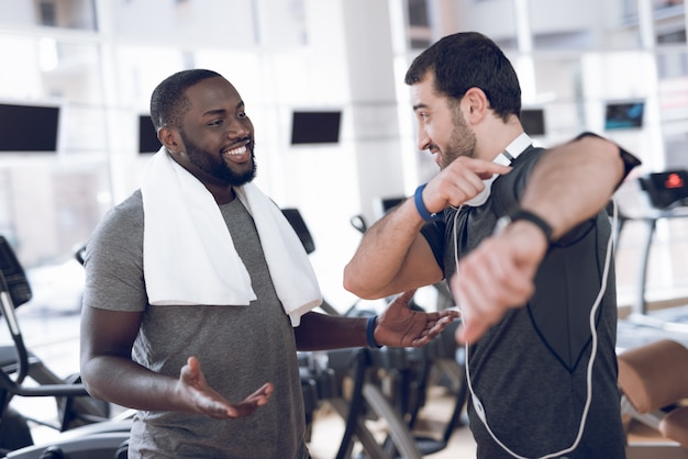 Man in headphones with a friend in the gym.