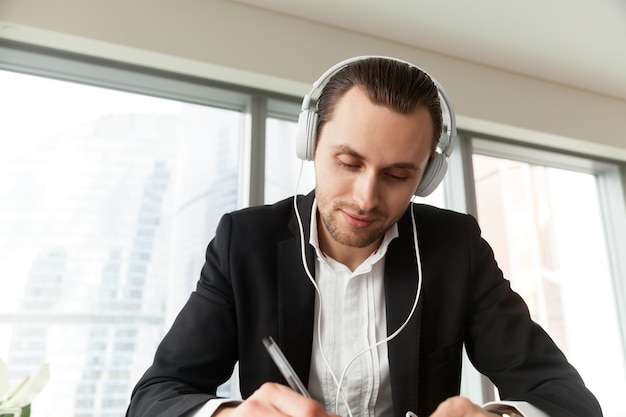 Man in headphones writing with pen at work desk