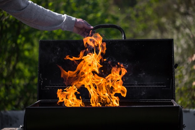 Man heats the bbq grill, preparing for grilling some kinds of meat