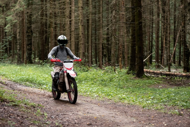 Man in a helmet on a motorcycle rides on a forest dirt road