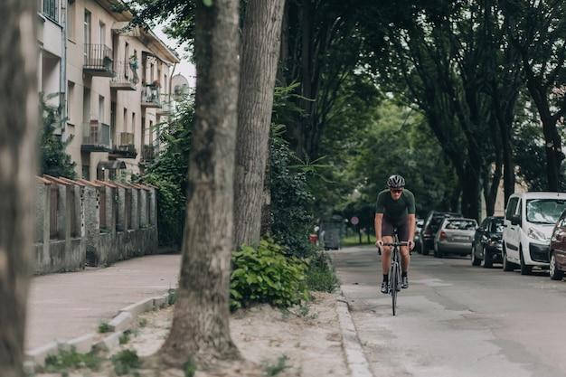 Man in helmet using bike for cycling on asphalt road