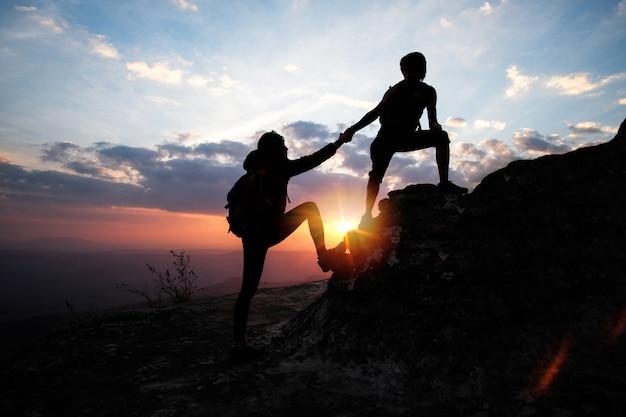 ハイキングアクティビティで山の上に女性を助ける男。チームワークの概念。