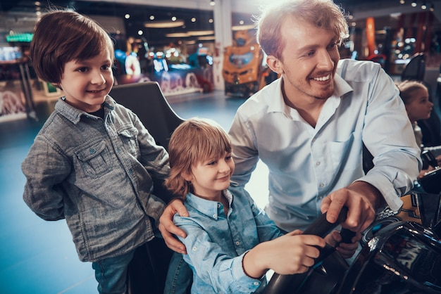 Man helping cute boy playing racing simulator game