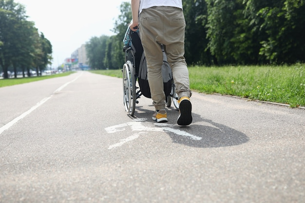 Man helping disabled person in wheelchair to walk on sidewalk