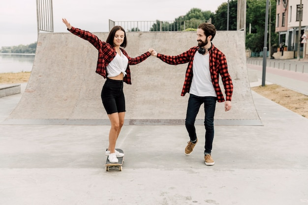 Man helping girlfriend ride a skateboard