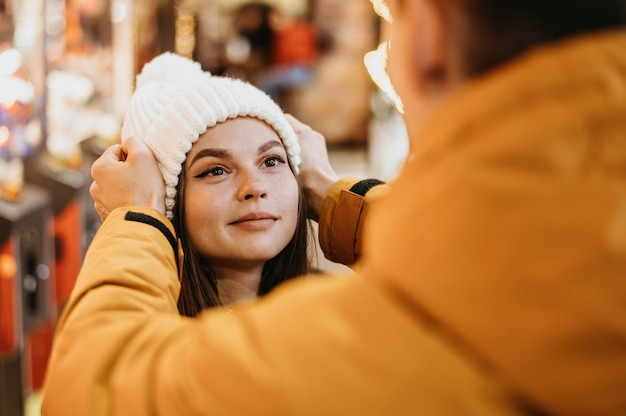 Мужчина помогает своей девушке надеть шапочку
