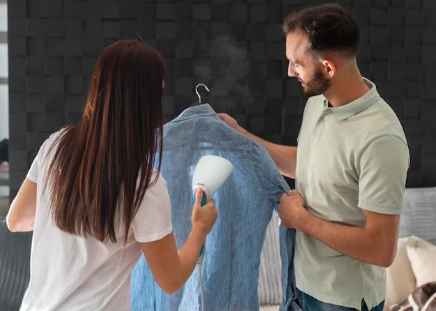 妻がシャツにアイロンをかけるのを手伝っている男