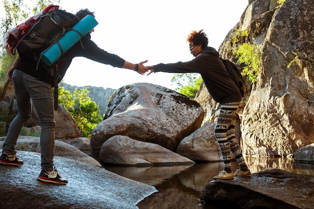 그의 여자 친구가 협곡에서 물을 넘어서 돕는 남자