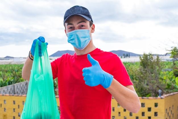 Мужчина помогает бедным людям давать им еду и воду в условиях карантина из-за коронавируса - молодой человек работает в одиночестве в медицинской и хирургической маске для предотвращения коронавируса