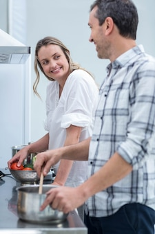 Man helping pregnant woman prepare food in kitchen