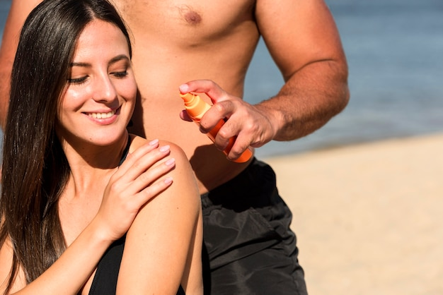 Man helping woman apply sunscreen at the beach