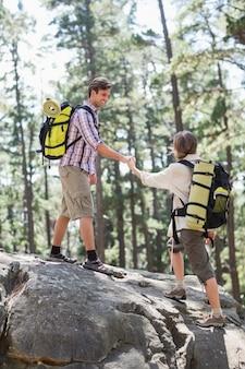 Мужчина помогает женщине подняться на скалу в лесу