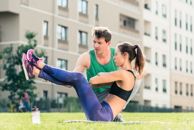 Man helping woman in doing crunches