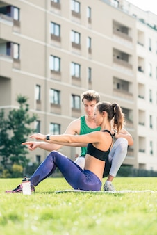 Man helping woman in doing exercise