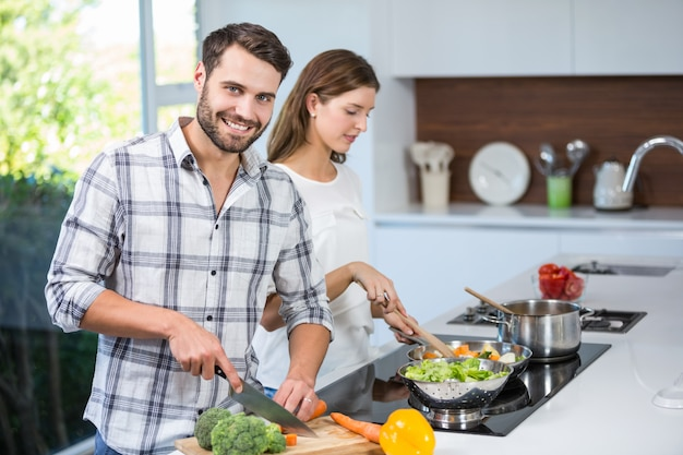 Man helping woman in preparing food at home