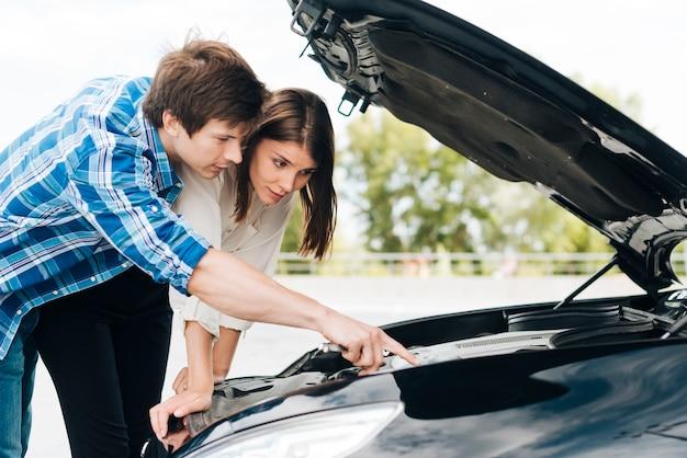 Man helping woman repair car