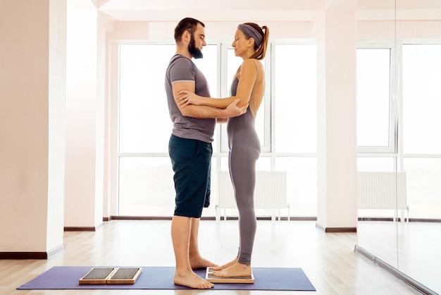 Мужчина помогает женщине стоять на доске садху-йоги