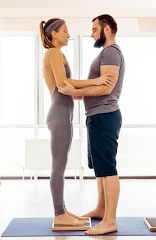 Мужчина помогает женщине встать на доску садху