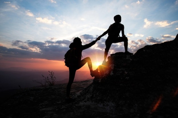 Man helping a woman to up on the mountain in hiking activity. teamwork concept.