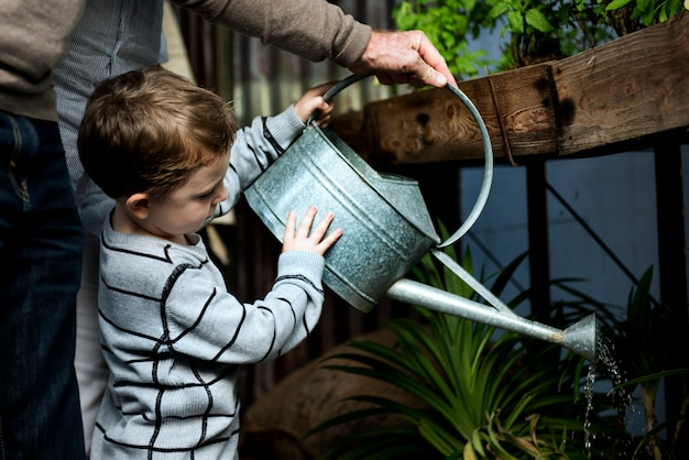 Man helping a young boy water the plants